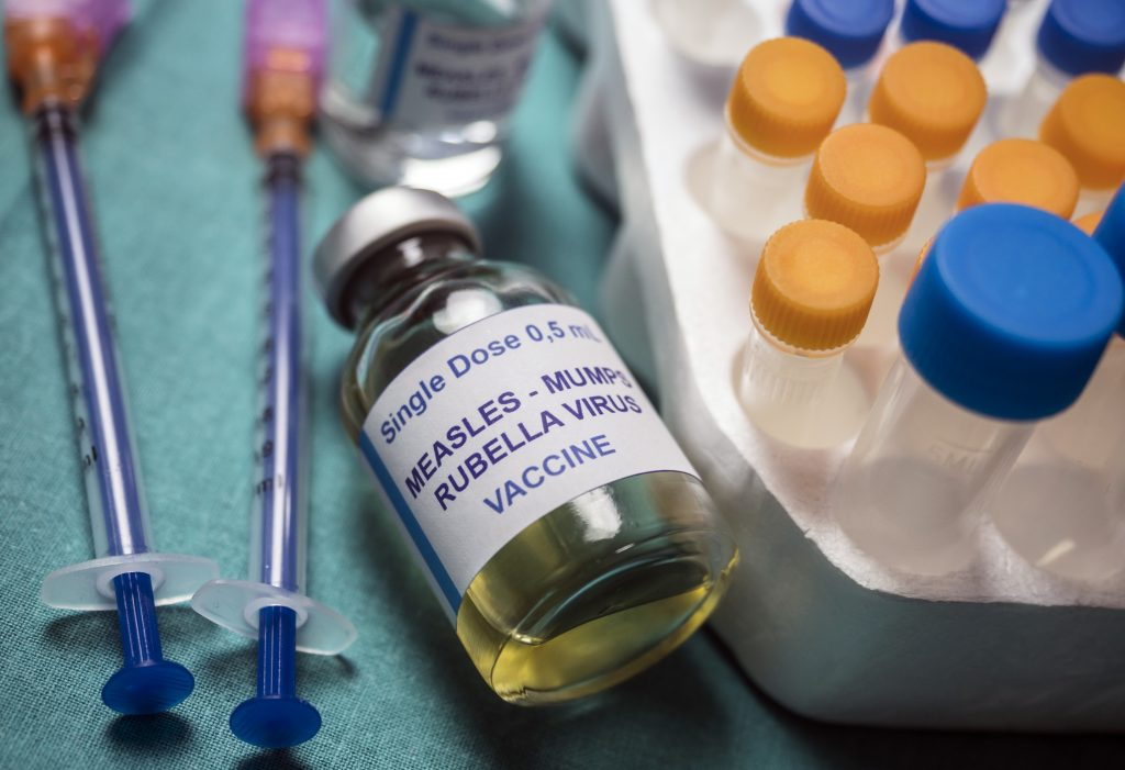 A picture of an MMR vaccine vial and vaccine syringe